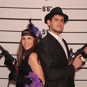 Cincinnati Murder Mystery party guests pose for mugshots